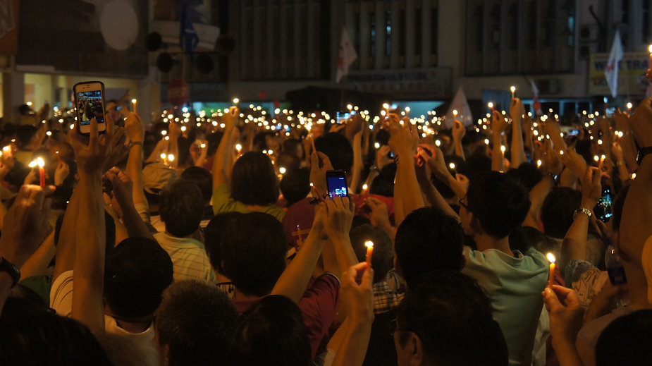 thousands of people holding candle ligh