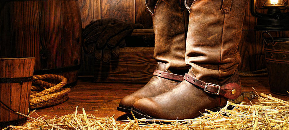 cowboy-boots-in-a-ranch-barn-olivier-le-
