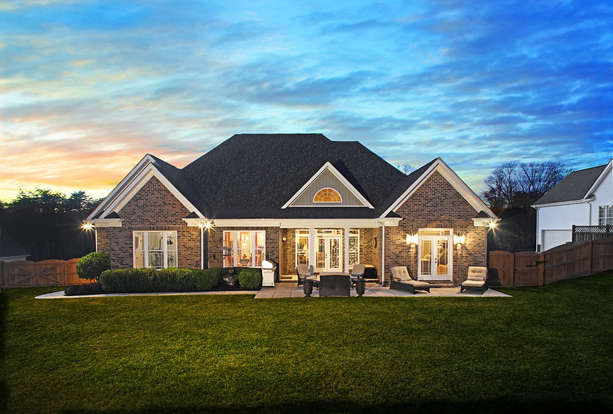 large brick house with stone patio, gree