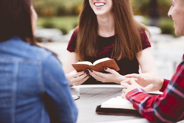 girls-sitting-around-table-reading-book-