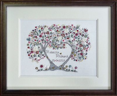 Wedding cross stitched textile with double off white conservation mount, silver copper picture frame and non reflective glass.