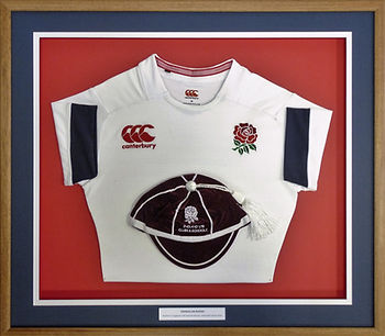 Framed rugby football shirt and cap.
