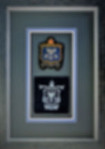 Picture framed military uniform badges.