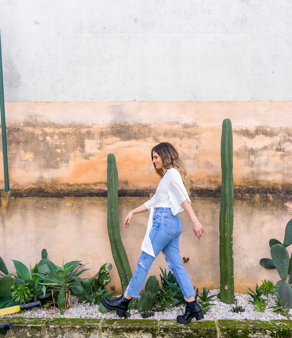 Girl walking along fence lines with cactus.