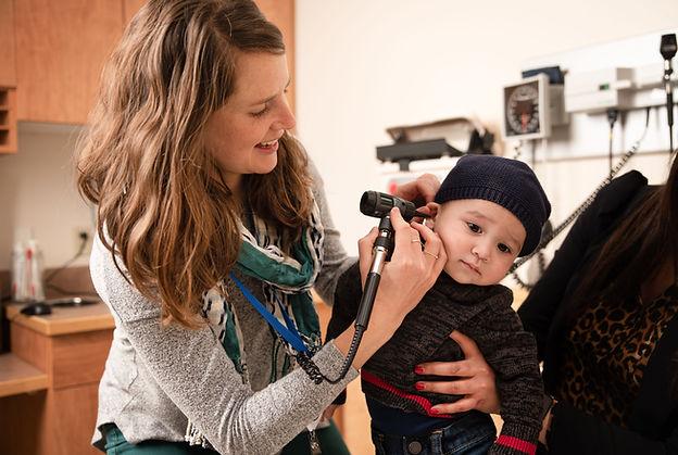 pediatrician looking into baby ear