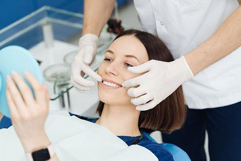 dentist-hands-and-happy-patient-looking-in-mirror-2021-06-02-04-35-26-utc.jpg