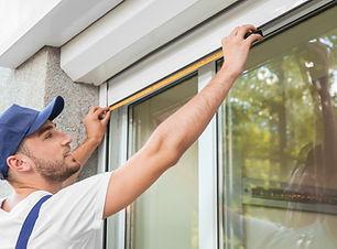 Man measuring window prior to installati
