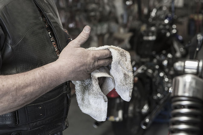 caucasian-man-repairing-motorcycle-wipin