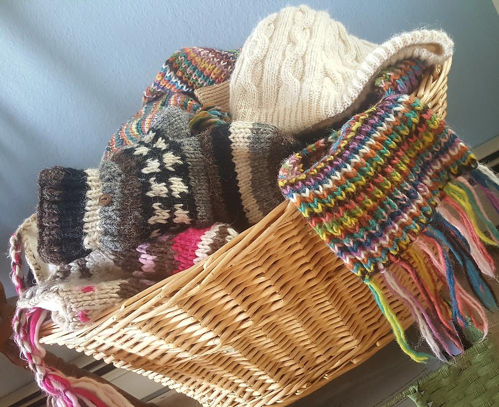 Basket of woolen mittens, hat, scarves spilling out