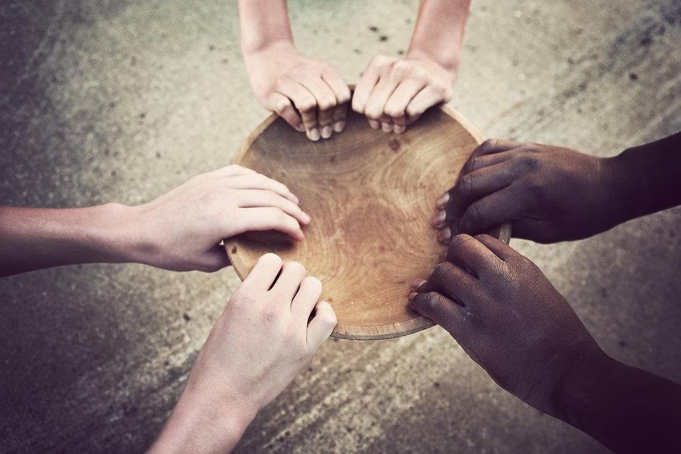 Mains tenant une assiette en bois
