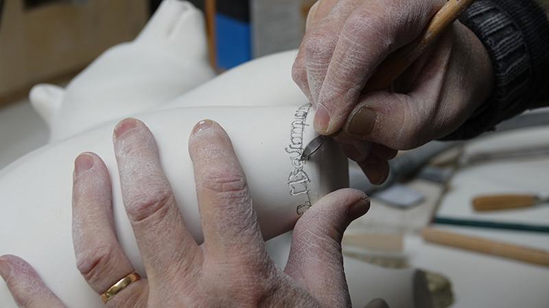 Michel Bassompierre inscrivant sa signature sur une sculpture en plâtre
