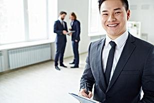 un homme asiatique en costume sourit
