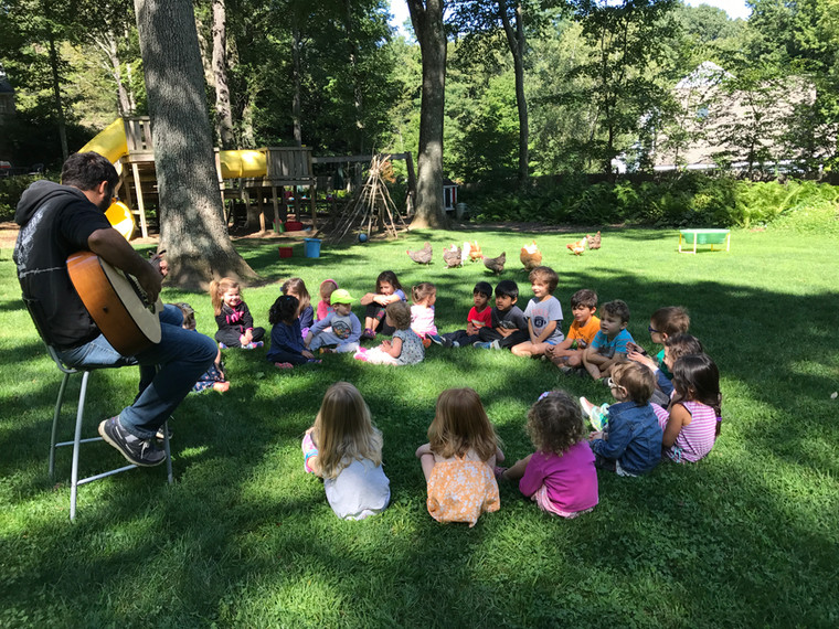 children sitting on the grass in a music lesson with the teacher playing the guitar