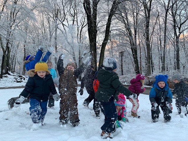 children having fun in the snow with snow flurries