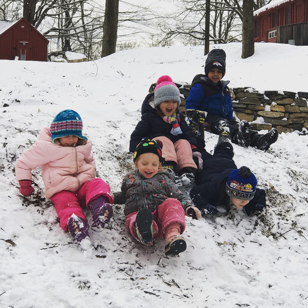 children sliding down a hill in the snow