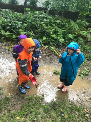 children playing in a muddy pool
