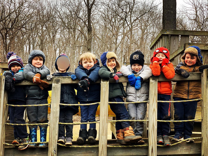 children look over a bridge at the camera