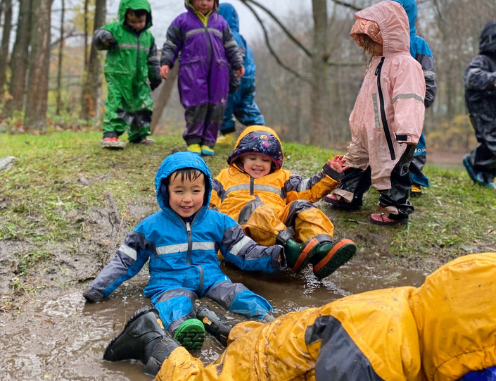 children sliding in mud