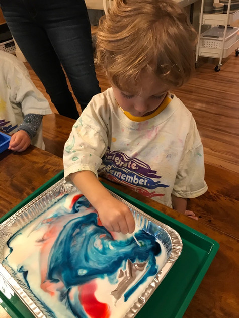 child painting with a stick cks