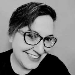 Black and white image of a woman with short hair who is smiling. She is wearing glasses and a dark shirt.