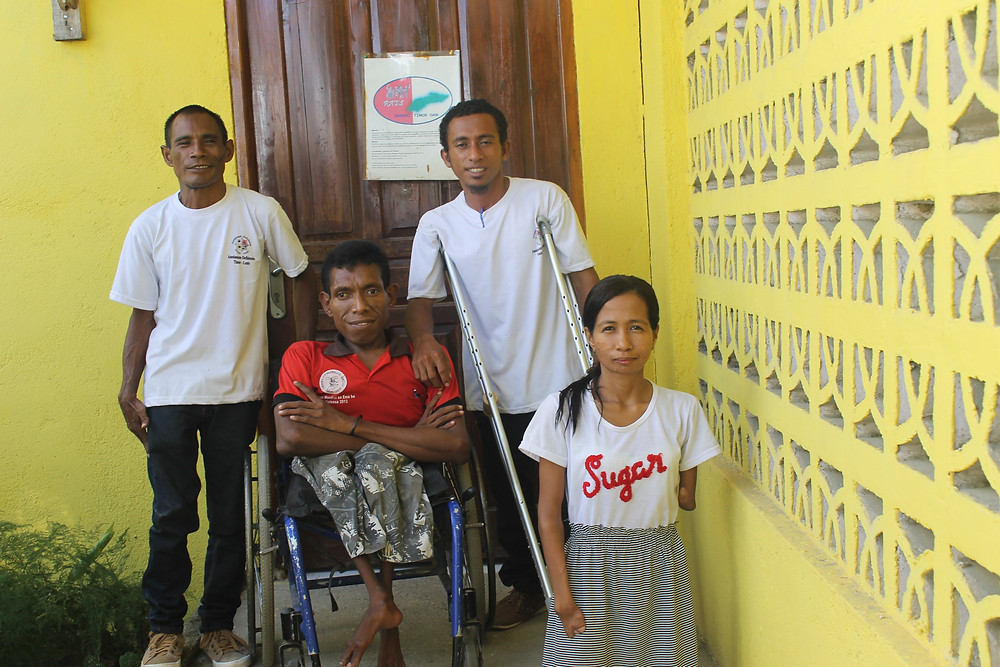 The photo shows four RHTO staff members standing outside the RHTO office. One staff member is a wheelchair user, one uses crutches, and two others have physical impairments but do not use assistive devices.