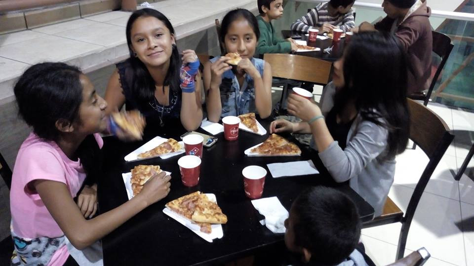 Filling bellies before the movie starts. Pizza is always a crowd-pleaser.
