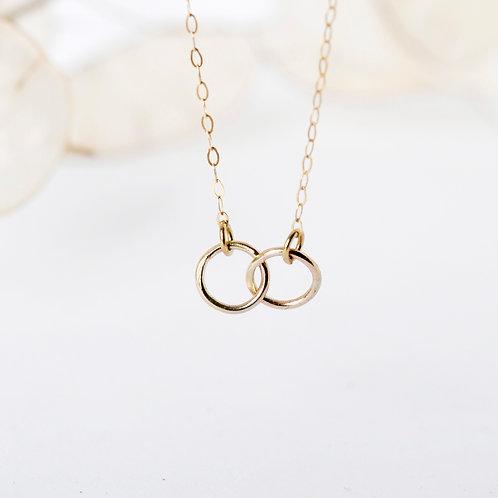 Goldkette mit verbundenen Ringen Frontansicht mit Trockenblumen