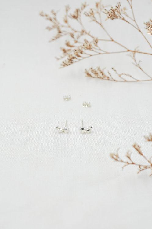 silberne Ohrstecker im Flatlay mit Verschlüssen und Trockenblumen