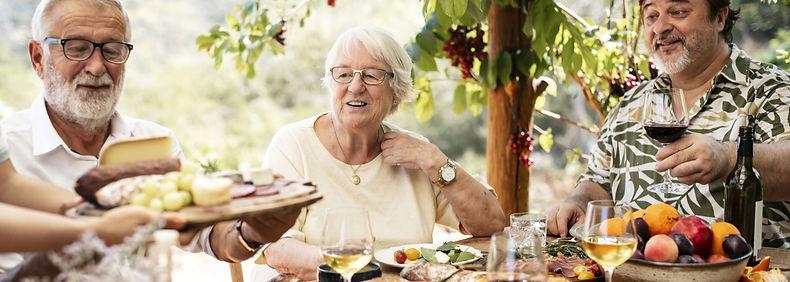 older adults eating dinner together outside