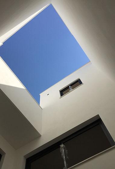 patio interior de la casa en color blanco y ventanas de aluminio lacadas a negro