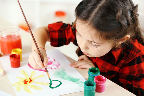 Cute little girl painting picture on hom