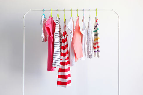 Children clothes on a rack on a light ba