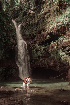 couple photographed infront of a waterfall
