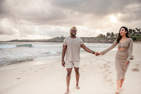 gorgeous couple holding hands on beach