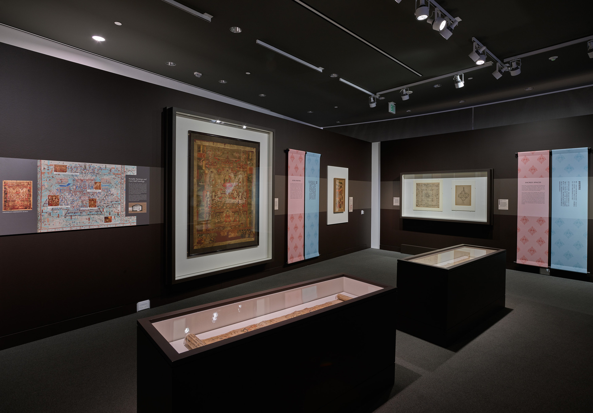 Exhibition featured large climate controlled shadowboxes, bilingual stretched fabric section texts and didactics explaining the connection of the artworks to the cave paintings.