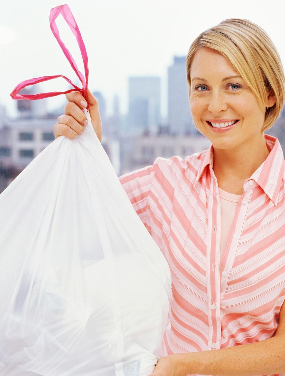 Smiling women holds up white garbage bag
