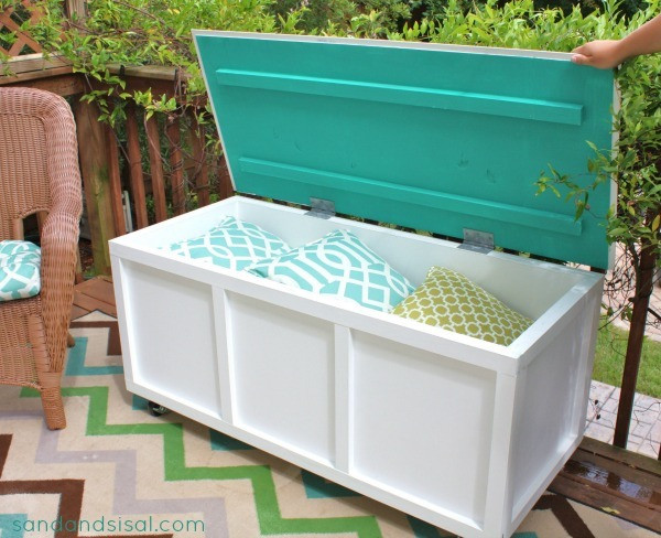 Blue and white patio storage box containing decorative pillows