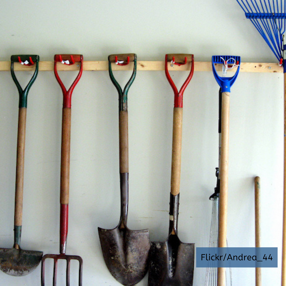 Large garden tools rakes and shovels hang in garage