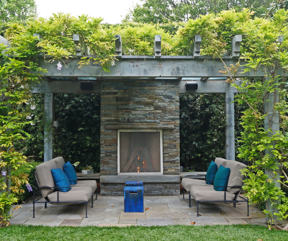 Pergola over stone patio with cushioned chairs and outdoor fireplace