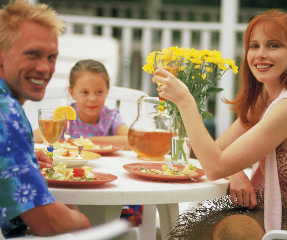 Young Mother and Father with daughter eating dinner on patio
