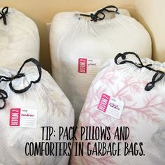 White garbage bag packed with pillows, comforters