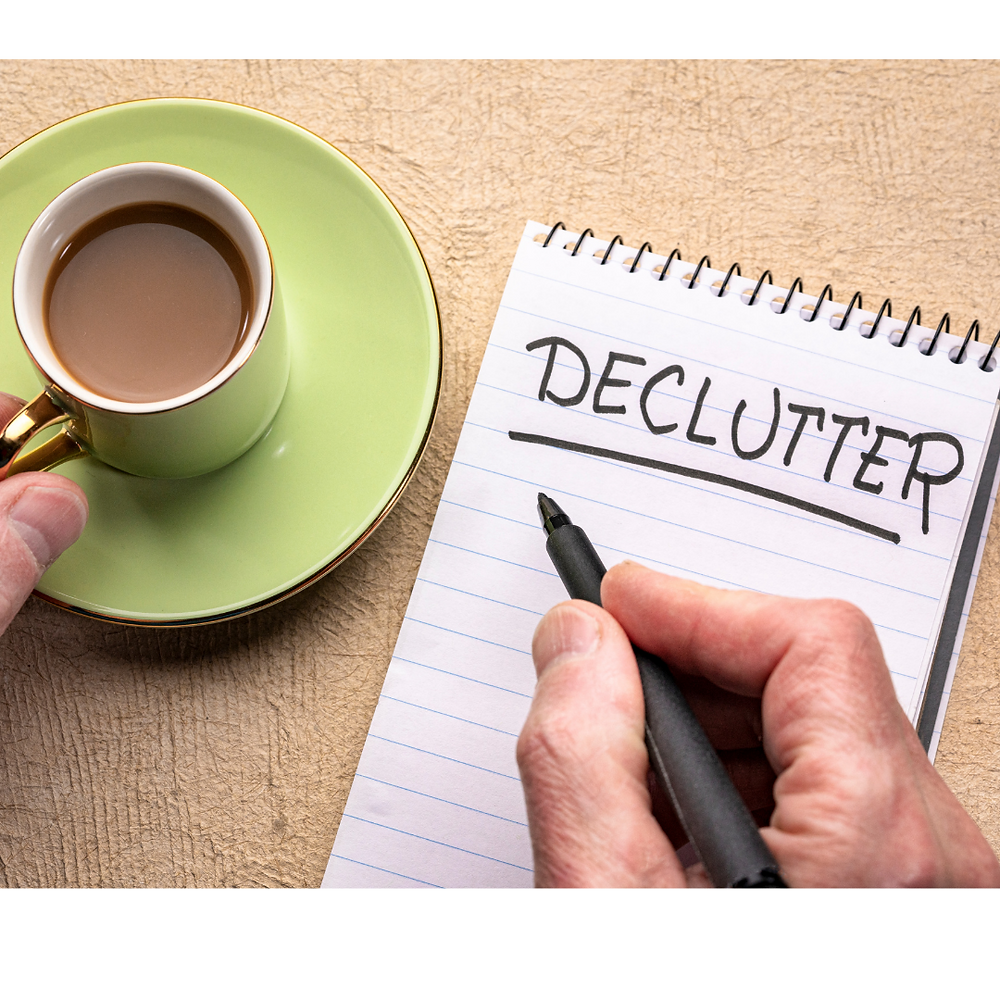 "Man with coffee and notebook. He writes ""Declutter"""