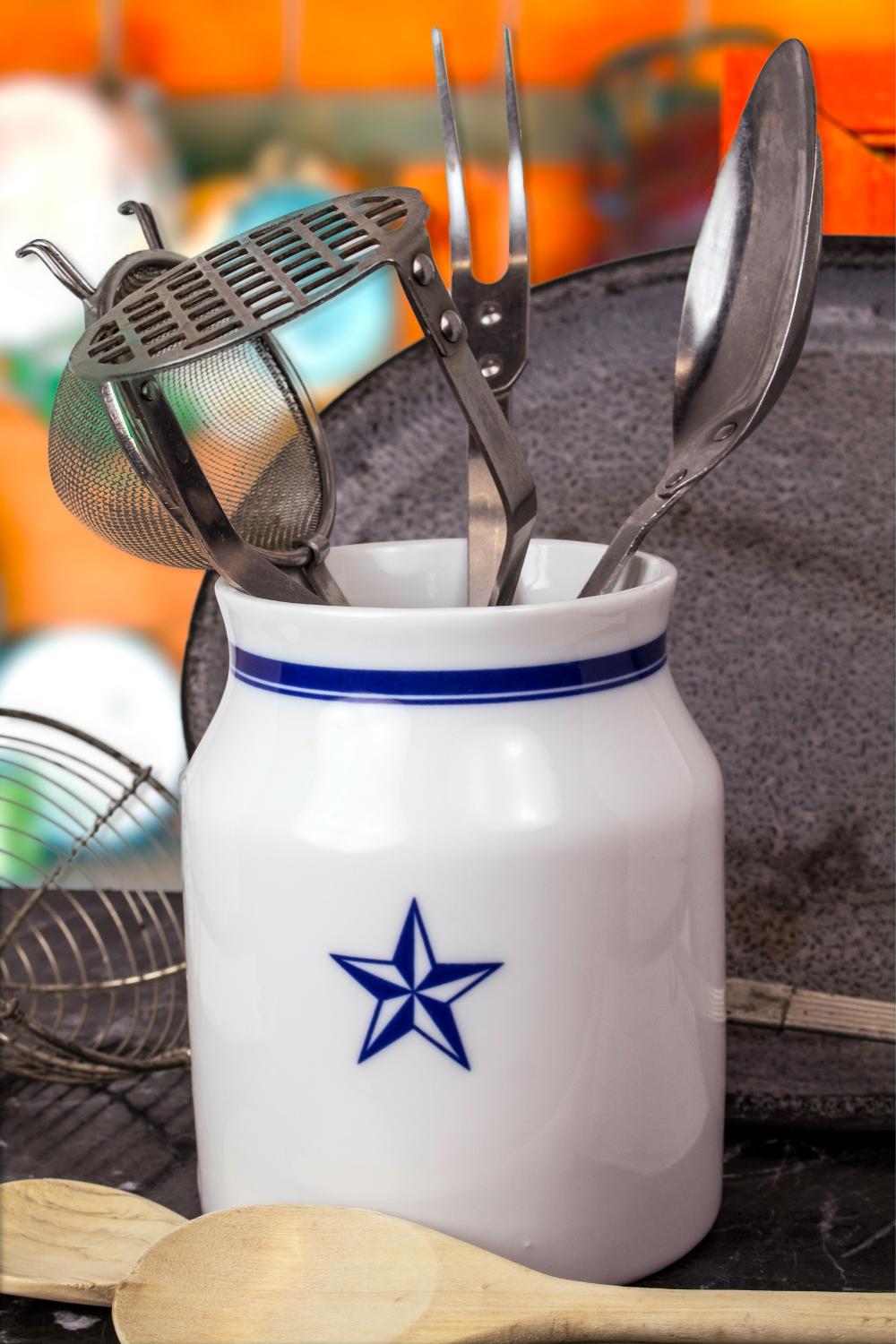 White clay pot with blue star holding kitchen utensils