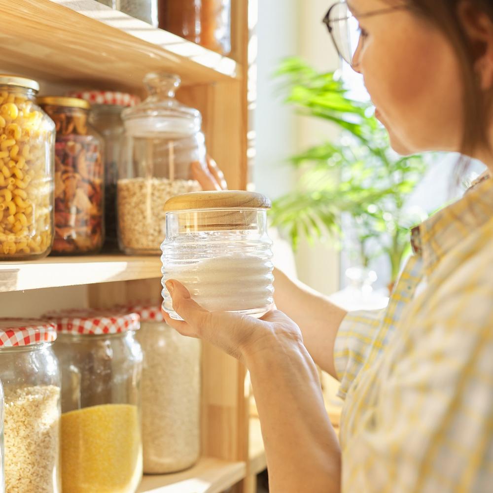 Women checking jars in pantry