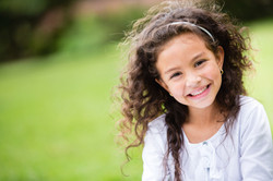 Sweet-little-girl-outdoors-with-curly-ha