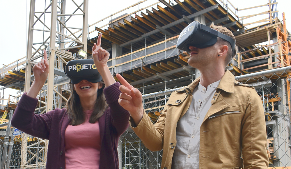 A man and a woman on a construction site, both wearing VR headsets and gesturing