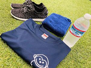芝生の上に靴とタオルと水と服