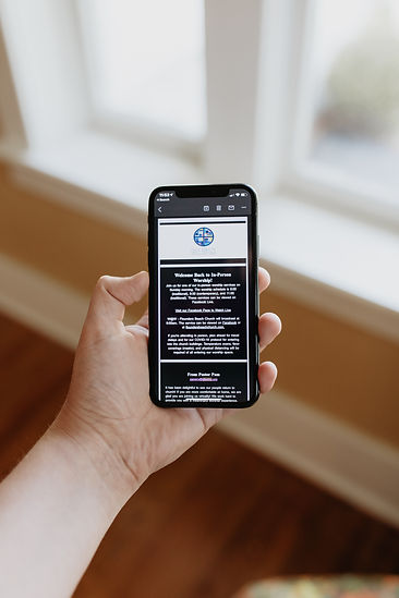 Hand holding phone with an image of the newsletter