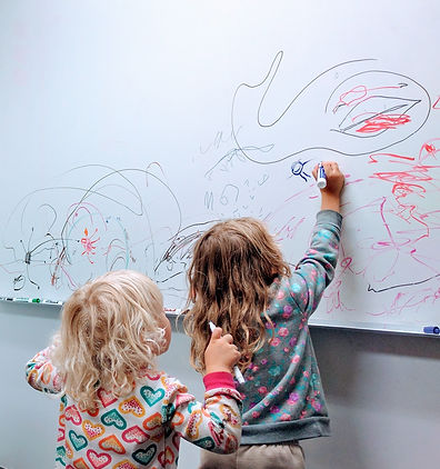 A photo of two young children drawing enthusiatically on a whiteboard filled with scribbles.