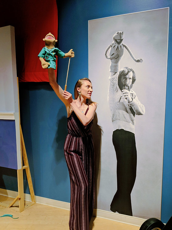 A photo of Layne at the Center for Puppetry Arts in Atlanta. She stands in front of a lifesize portrait of Jim Henson and mirrors his pose—arms raised while holding a puppet and puppeteering.